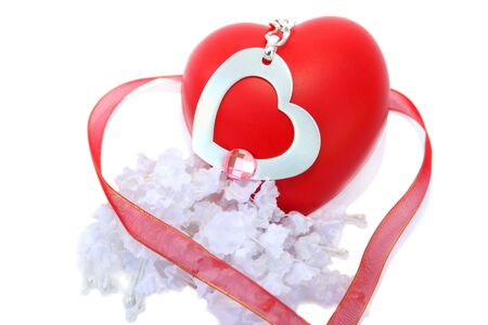 Red valentine heart, ribbon,necklace with metallic heart,white fabric flowers on white background. photo