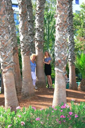 Pretty blond girl and her mother in tropical park. photo