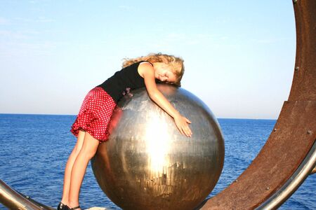 Blond girl on the metallic ball. photo