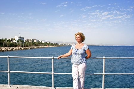 Pretty blond woman on the pier at the Mediterranean sea in Cyprus. photo