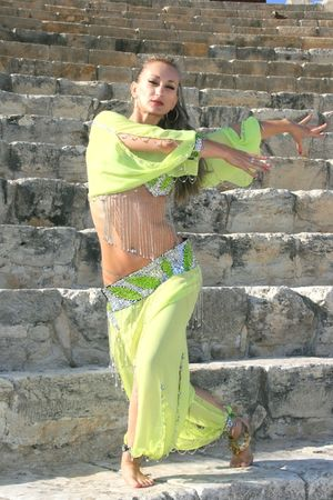 Beautiful belly dancer in green on the ancient stairs of Kurion amphitheatre in Cyprus. photo