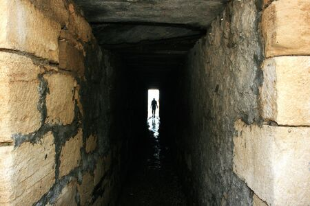 scared man: A figure walking out of a dark tunnel to bright light. Stock Photo