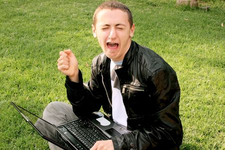 Crying boy with laptop on the grass. photo