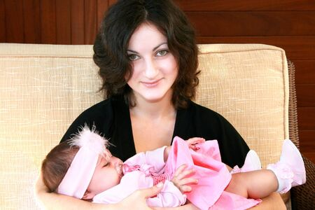 Pretty brunette girl with sleeping baby. photo