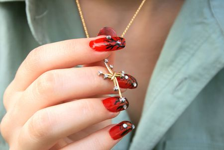 nailart: Nail-art fingers holding golden cross with necklace. Stock Photo