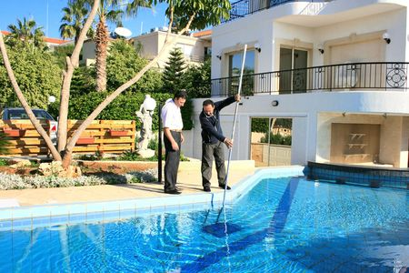Swimming pool cleaner and property owner. Stock Photo - 5798593