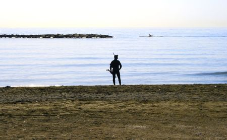 Diver man silhouette at the shore in twilight. Stock Photo - 5813732