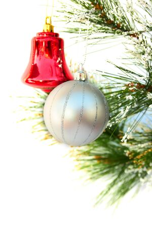showy: Christmas ball and bell hanging on fir-tree branch.