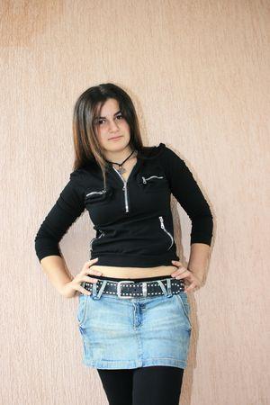 Fille assez brunette en veste noire et des jeans.