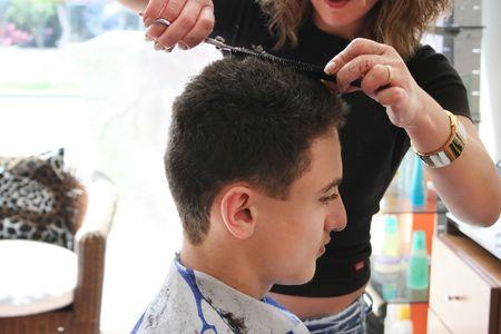 Hairdresser cutting teens hair in beauty saloon. photo