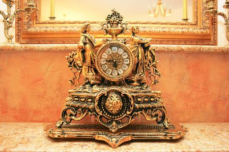 Ancient style clock on the marble table. photo