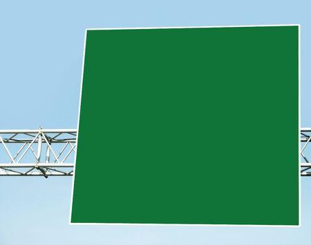 Empty green billboard on blue sky background. photo