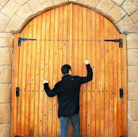 porte ancienne: Adolescent cognement porte de vieux bois � Chypre.
