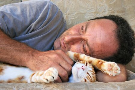 gape: Relaxing man and cat on sofa.