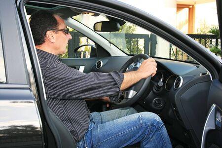 Man in new black car. photo