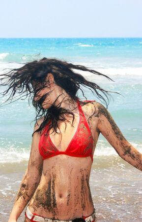 Pretty dirty brunette girl on beach. photo