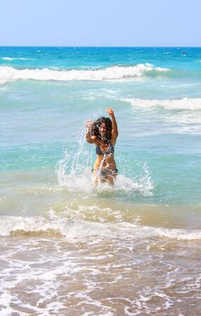 Pretty brunette girl in blue sea. photo