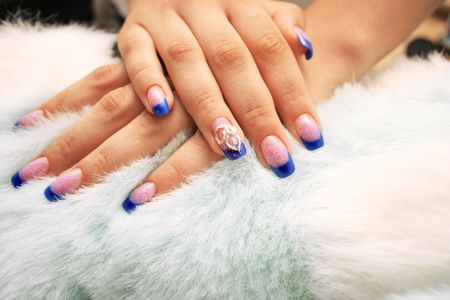 Woman hands on fur background.
