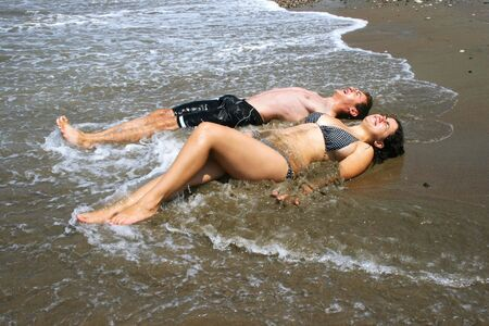 Couple enjoying cold sea water on beach. photo