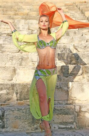 Beautiful belly dancer in green on the ancient stairs of Kourion amphitheatre in Cyprus. photo