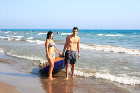 Couple with boat walking at  the sea. photo
