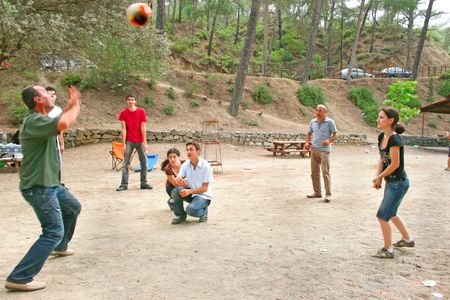 family and friends: Group of young people playing ball in the forest.