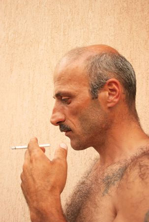 hairy male: Smoking man vertical picture. Stock Photo