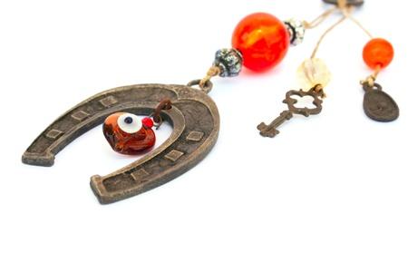 Rusry old horseshoe with eye bead and key isolated on white background. photo