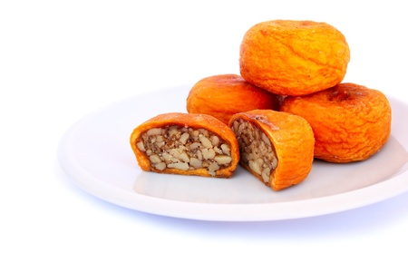 Dried peaches stuffed with nuts in plate isolated on white background. photo