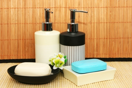 Soap dispensers and bars on bamboo. photo