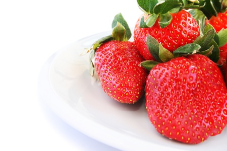 Strawberries in plate isolated on white background. photo