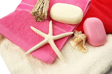 Soaps, shell, seastar on colorful towels. photo