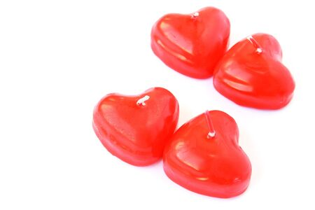 Heart shape red candles isolated on white background. photo