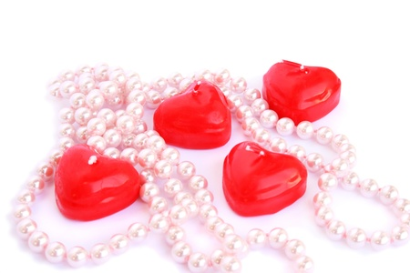 Heart shape red candles and necklace isolated on white background. photo