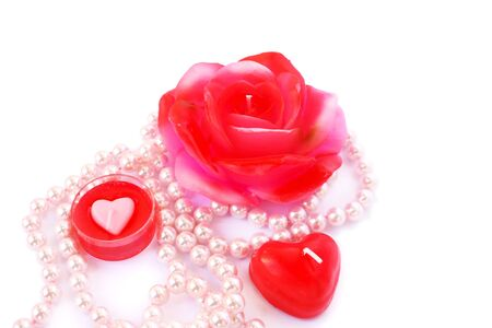 Heart and rose shape red candles, necklace isolated on white background. photo