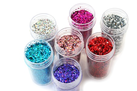 Colorful nail glitters isolated on white background. photo