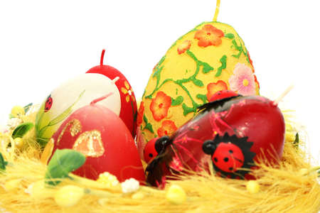 Easter colorful candle eggs nest isolated on white background. photo