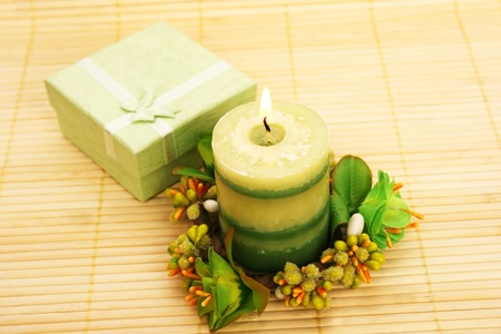 Candle, flowers and present box on bamboo background. photo