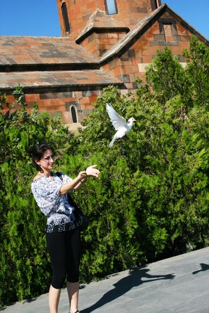 Pretty woman releasing a pigeon at Khor Virap church in Armenia.  photo