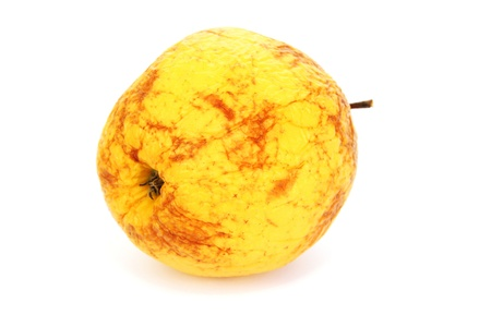 Old yellow apple isolated on white background. photo