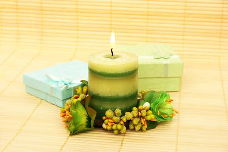 Candle, flowers and present boxes on bamboo background. photo