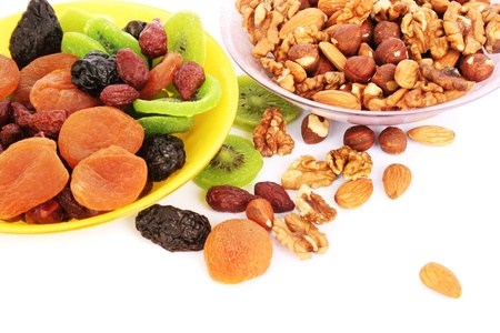 Dried fruits and nuts  in vases  isolated on white background. photo