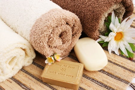 Towels and olive oil soap with aloe vera, flowers on mat background.. Stock Photo - 13559640