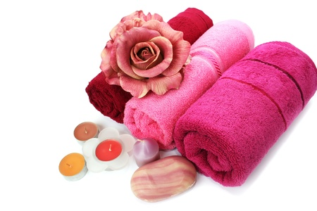 Towels, candles, soaps and flower isolated on white background.