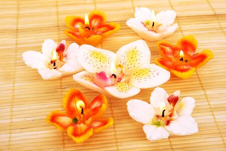 Orchid candles on bamboo background. photo
