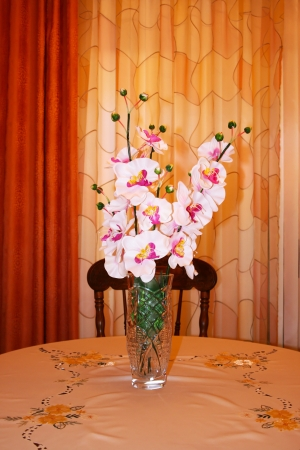 Orchids in vase on the table. photo