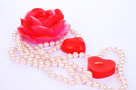 Heart and rose shape red candles, necklace isolated on grey background. photo