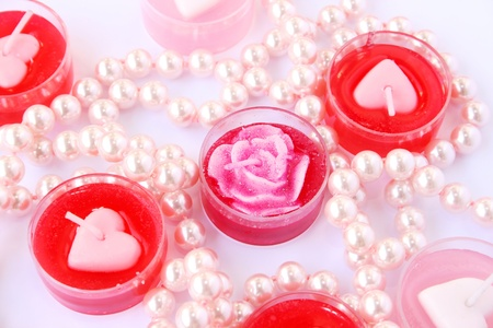 Heart shape red and pink candles with necklace  isolated on grey background. photo