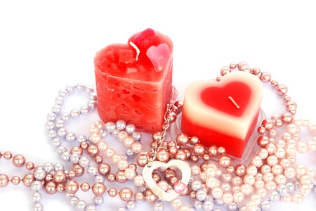 Heart shape red candles and necklaces isolated on white background. photo