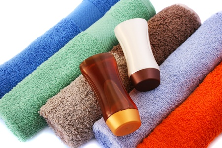 Shampoo bottles and colorful towels on white background. photo